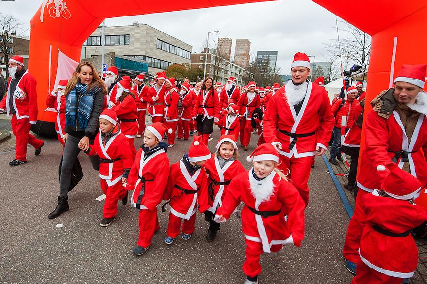 Nederland, Amsterdam, 21 dec 2014<br /> Santa Run op het Gelderlandplein, Amsterdam. Warming up voordat de run begint.<br /> De Santa Run is een fun-run van 3000 meter en wordt gelopen door als kerstman verklede renners die daarmee geld ophalen voor, in dit geval, het Leerorkest en het Liliane Fonds. De Rotary Club organiseert wereldwijd Santa Runs om geld in te zamelen voor goede doelen.<br /> Foto: (c) Michiel Wijnbergh