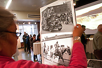 """Angela Buck holds pictures from the Ellensberg Rodeo as a slideshow of images of the Columbia river scroll in front of them at an exhibit called """"Sacred Spaces"""" at the Central Washington University Museum of Culture and Environment in Ellensberg, Wash. on February 3, 2011.  (photo credit Karen Ducey)"""