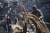 Priests and family members prepares the pyre for the dead while the family members wait next to it outside the Pashupathi Nath Temple in capital Kathmandu, Nepal