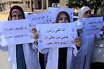 Palestinian employees of the health ministry hold placards during a protest against not receiving their salaries, in Gaza City on June 30, 2014. Many issues involving the Strip, such as the fate of former employees of the Hamas government, have yet to be addressed by the new unity government. Photo by Mohammed Asad