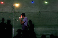 BENIC&Agrave;SSIM, SPAIN - A festival goer lights up a cigarette aside one of the many fences that criss-cross the festival site. ..Described by some as a Mediterranean Glastonbury, the Festival Internacional de Benic&agrave;ssim (FIB) is the largest music festival outside the UK to target British visitors. In 2010, seven of the eight main headline slots were filled by English bands...A small coastal town of 13,000 inhabitants, Benic&agrave;ssim hosted some 200,000 visitors in 2009, with 40% of those believed to be coming from the UK. In 2010, attendances fell to 127,000 visitors but the percentage of UK visitors is believed to have risen.