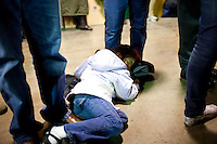 A girl sleeps on the floor at her mother's feet as Republican presidential candidate Newt Gingrich speaks at a campaign town hall meeting at Level 10 Apparel on Monday, December 19, 2011 in Hiawatha, IA.