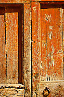 Detail of an old wooden door scratched and broken in Villa Saletta, an abandoned town in the Pisa county, Italy