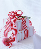 A christmas present wrapped in red and white striped paper and tied with a red and white gingham ribbon