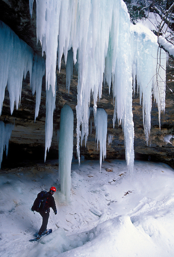 An ice climber hikes a trail beneath hanging ice formations on cliffs at Pictured Rocks National Lakeshore near Munising, Mich.