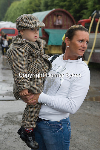 Brigg Horse Fair. Brigg Lincolnshire England 2009. Gypsy mother and two year old son wearing best clothes, a  smart tweed suit and flat cap.
