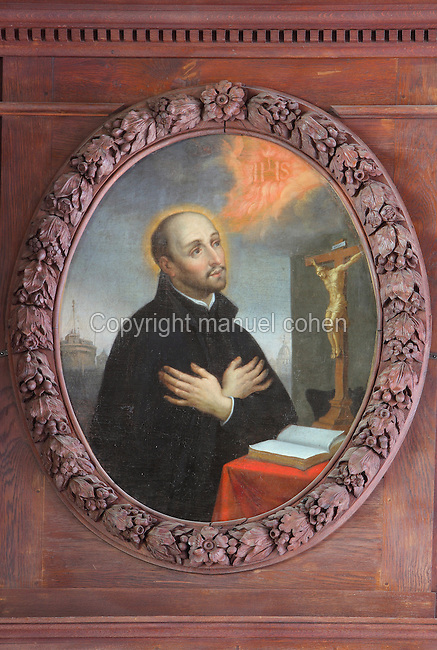 Painting of St Ignatius of Loyola, 1491-1556, founder of the Society of Jesus or Jesuit Order and its first Superior General, in prayer, by Jean Helart, 1618-85, French painter, in a carved wooden garland frame set in the wooden panelling of the refectory of the Ancien College des Jesuites or Former Jesuit College in Reims, Marne, Champagne-Ardenne, France. The College was built 1619-78 and is now the Euro-American campus of Sciences Po, or the Institut d'Etudes politiques de Paris, and the FRAC Champagne-Ardenne. It is listed as a historic monument. Picture by Manuel Cohen