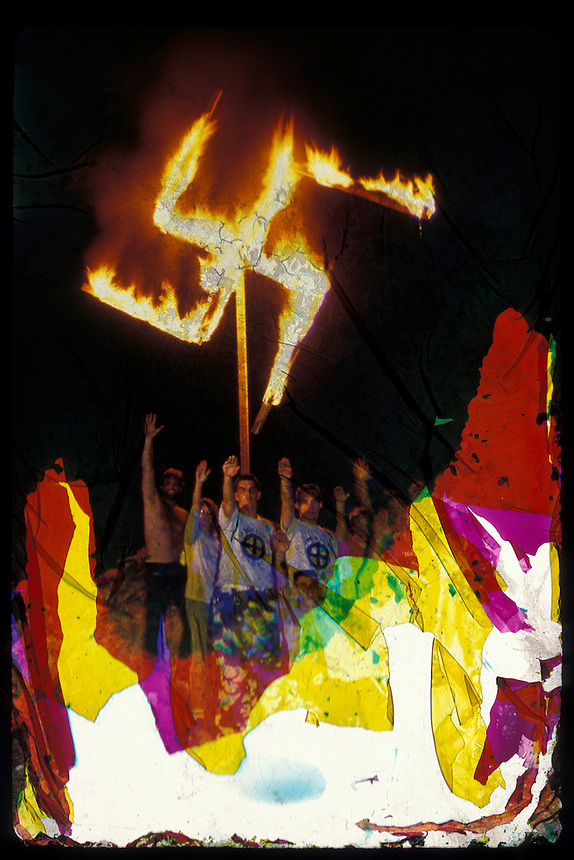 Neo-Nazis pose in front of a burning swastika during a secret rally in Florida in the 1980s. The extreme colors result from layers of emulsion peeling away in a random pattern. A historical photo, damaged artistically by flooding caused by Hurricane Sandy in October, 2012.
