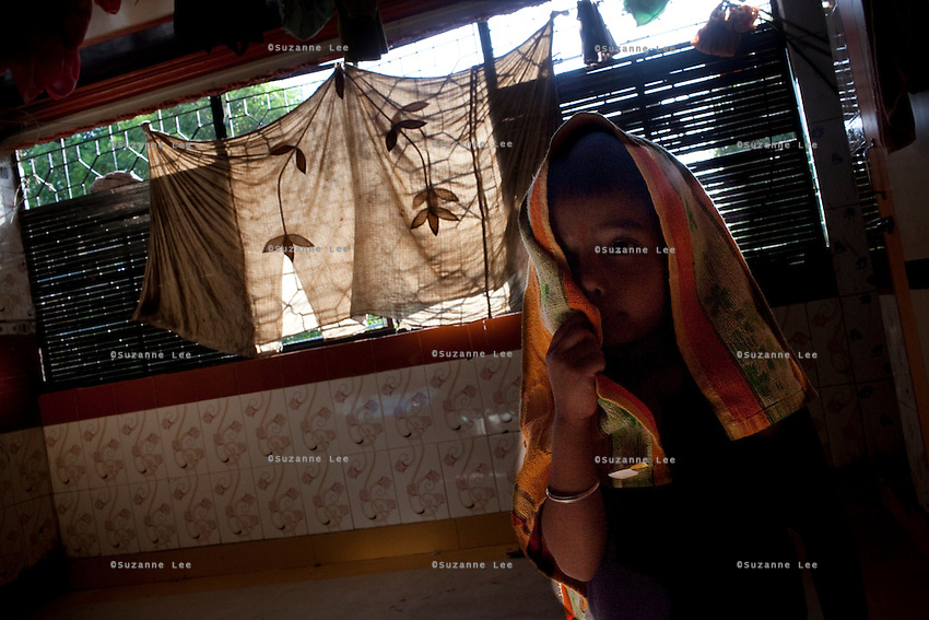 A child stands by the window of a brothel on 28th September 2010, on GB Road, Delhi's red light district, India...Mr. Kailash Pathak, a Brahmin priest, has travelled to Delhi from his village in New Jalpaiguri, West Bengal, to look for his missing daughter, Khushbu Pathak aged 13, who was last seen in the custody of his neighbours in February this year and believed to have been sold to brothels in the capital, Delhi. The accused neighbours have since been arrested in Delhi but the girl is yet to be found. Photo by Suzanne Lee