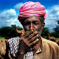 A Raika man smokes a bidi cigarette. The Raika are an ancestral caste of camel breeders in Rajasthan. Due to the increased cost of feeding and shelter, more and more Raika are being forced to sell off their camels, often for camel meat, which was once considered taboo.