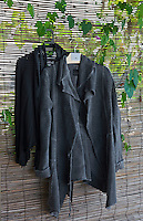 A couple of jackets hang from a bamboo blind