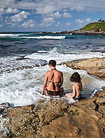 A mother and daughter enjoy the wash of the tide at Ho'okipa Beach Park, Maui.