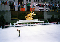 A solo skater gestures passionately on the ice rink of Rockefeller Center in New York City
