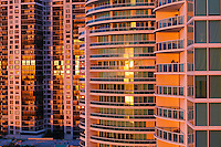 Miami, Florida condominium buildings reflect the warm light of the rising sun.