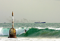 A surfer catches a wave to surf behind the pylon at Cottesloe Beach.