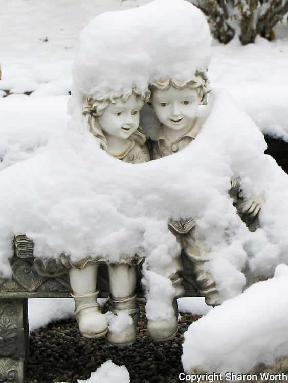 A garden figurine of kids on a bench slowly returns to view as the previous day's snow starts to melt.