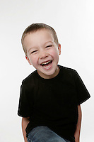 Five year old boy laughing giggling smiling and having fun in the studio.