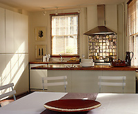 A contemporary kitchen has floor to ceiling cupboards and a rustic style dining area