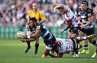 Kyle Eastmond of Bath Rugby offloads the ball after being tackled. West Country Challenge Cup match, between Bath Rugby and Gloucester Rugby on September 26, 2015 at the Recreation Ground in Bath, England. Photo by: Patrick Khachfe / Onside Images