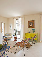 A bright yellow sideboard adds a dramatic touch to the otherwise neutral palette of the living area