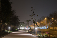 Fog slowly rolls in on a calm night at the Harbor Boulevard Cornerstone Bike Trail in Costa Mesa, California.  No cars are visible on Harbor Boulevard, thanks to the late hour.  The pathway is lit up with bright white lights leading off into the foggy distance, and the street lights and trees clearly show the foggy nature of the night.  The sky is a mix of deep-blue with fog-white over it.  The landscape architecture work on the project was done by David Volz Design.