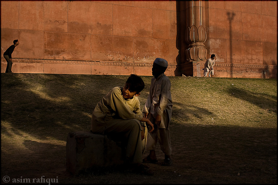 playing cricket, considered to be the national sport, along the magnificent walls of the grand badshahi mosque in the old city of lahore