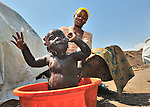 A woman bathes her child in a camp in rebel-held territory in the eastern Congo. Families displaced by fighting between rebel Tutsi General Laurent Nkunda and the Congolese military took refuge in this camp they established in the shadow of a United Nations base in the village of Kiwanja. According to aid workers and human rights groups, rebel soldiers executed some 150 people here in a 24-hour period in early November. The killings took place half a mile from the UN base, yet the 120 UN peacekeepers, part of the largest UN peacekeeping contingent in the world, did not take any action to stop the violence. ..