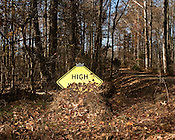 November 20, 2009. Snow Camp, North Carolina..A high water sign is covered by fall leaves.