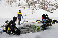 Eistaucher sitzen am Eisloch, scuba diver sitting at hole of frozen lake