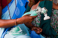 Pahari Tharu, 52, a female community health worker, holds some of her midwifery equipment as she speaks of family planning and pregnancy health to a group of teenaged mothers and child brides in Bhaishahi village, Bardia, Western Nepal, on 29th June 2012. In Bardia, StC works with the district health office to build the capacity of female community health workers who are on the frontline of health service provision like ante-natal and post-natal care, and working together against child marriage and teenage pregnancy especially in rural areas. Photo by Suzanne Lee for Save The Children UK