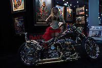 New york, United States. 18th January 2013 -- A woman poses for pictures during The International Motorcycle Show in New York. -- BMW, Ducati, Harley-Davidson, Honda, Kawasaki, Suzuki, Star, Triumph, Victory, Yamaha and more have all utilized the International Motorcycle Shows to unveil new motorcycles and concept vehicles to the world. Photo by Eduardo Munoz Alvarez / VIEWpress.