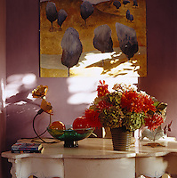 An arrangement of Chrysanthemums and Hydrangeas stands on this French white-painted console table, beneath a contemporary painting