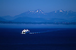 Ferry boat crossing waterway with Puget Sound and Olympic Mountains on a sunny day Seattle Washington State USA