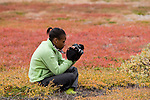 Chisomo examines one of her photographs while sitting on a carpet of dwarf birch and willow during a landing in Greenland. Central to the expedition was the use of art to communicate climate change and bring the message back home to their school.