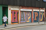 "Middlesex Street East End London E1. Alphabet Street project ""HAPPY"" on shop shutters work by street artist Ben Eine (real name Ben Flynn). Man walking past."