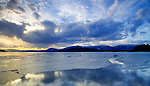 Idaho, North, Bonner County, Sandpoint. Ice thaws on Oden Bay of Lake Pend Oreille under a setting sun. Schweitzer Mountain in the distance.