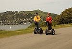 Couple on Segways, each on a Segway, on Angel Island State Park in San Francisco Bay, California, CA. Model released..Photo camari201-70409..Photo copyright Lee Foster, www.fostertravel.com, 510-549-2202, lee@fostertravel.com.