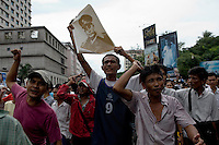 People line the streets to show their solidarity with protesting Buddhist monks calling for the overthrow of the country's military junta. One man holds up a poster of General Aung San, father of opposition leader Aung San Suu Kyi, architect of Burma's independence and founder of the Burmese army.