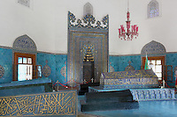 Interior of the Green Tomb or Yesil Turbe, mausoleum of the 5th Ottoman Sultan Mehmed I Celebi, showing the mihrab and tombs, Bursa, Turkey. The tomb was built by Mehmed's son and successor Murad II following Mehmed's death in 1421 and is so named because of the green-blue tiles which cover the exterior. The architect, Haci Ivaz Pasha, designed the tomb and the Yesil Mosque opposite. The chandelier is a recent addition to the tomb. Picture by Manuel Cohen