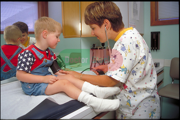 doctor examines young boy's blood pressure during examination