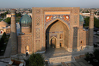 """Aerial view of the Sher-Dor Madrasah, 1619-36, Samarkand, Uzbekistan, pictured on July 15, 2010 at sunset which lights up the elaborately tiled facade and domes. The Sher-Dor Madrasah, commissioned by Yalangtush Bakhodur as part of the Registan ensemble, and designed by Abdujabor, takes its name, """"Having Tigers"""", from the double mosaic (restored in the 20th century) on the tympans of the portal arch showing suns and tigers attacking deer. Samarkand, a city on the Silk Road, founded as Afrosiab in the 7th century BC, is a meeting point for the world's cultures. Its most important development was in the Timurid period, 14th to 15th centuries. Picture by Manuel Cohen."""
