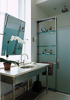 This en suite bathroom has a chrome shelving unit incorporated into the opaque glass of the shower and a marble topped wash-stand