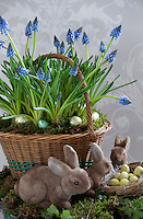 A vintage Easter still life of grape hyacinths in a wicker basket surrounded by toy rabbits and small chocolate eggs