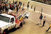 INDIANAPOLIS, IN - MAY 30: A tow truck carries the McLaren M16A 3/Offenhauser TC of David 'Salt' Walther after his crash on the opening lap of the 1973 Indy 500 on May 30, 1973, at the Indianapolis Motor Speedway in Indianapolis, Indiana.