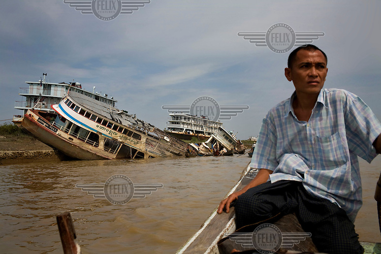 A man passes a group of damaged ships on the banks of the Yangon River. The lack of cargo ships is one of the major handicaps to delivering aid into the delta region. Cyclone Nargis hit Burma on 02/05/2008.