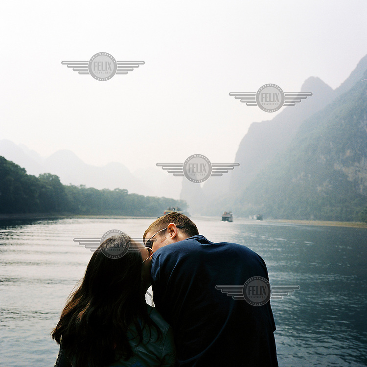 A tourist couple kiss on a cruise on the Li River as they make there way towards Yangshuo.