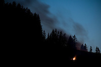 Small midsummer fire burns on hillside in mountains of Austria