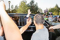 Real estate mogul and Republican presidential candidate Donald Trump waves from a vehicle as he leaves a rally at the Weirs Beach Community Center in Laconia, New Hampshire.