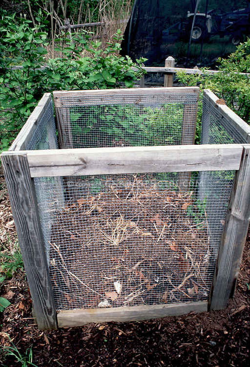 Composting in airy mesh metal and wooden hand made compost bin