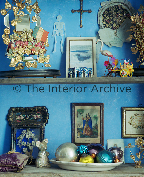 Brightly coloured metallic baubles and religious imagery are amongst the things displayed on this open shelving